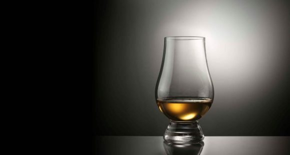 Whisky Live glass on empty black graded background